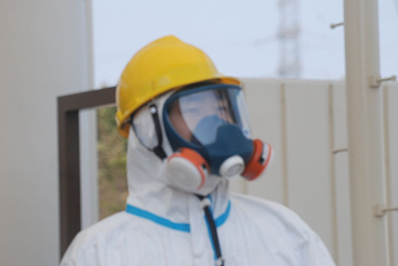 Gate guard in a hazmat suit, helmet and dual intake respirator following the 2011 Fukushima nuclear power plant disaster. Credit: VOA S. Herman)