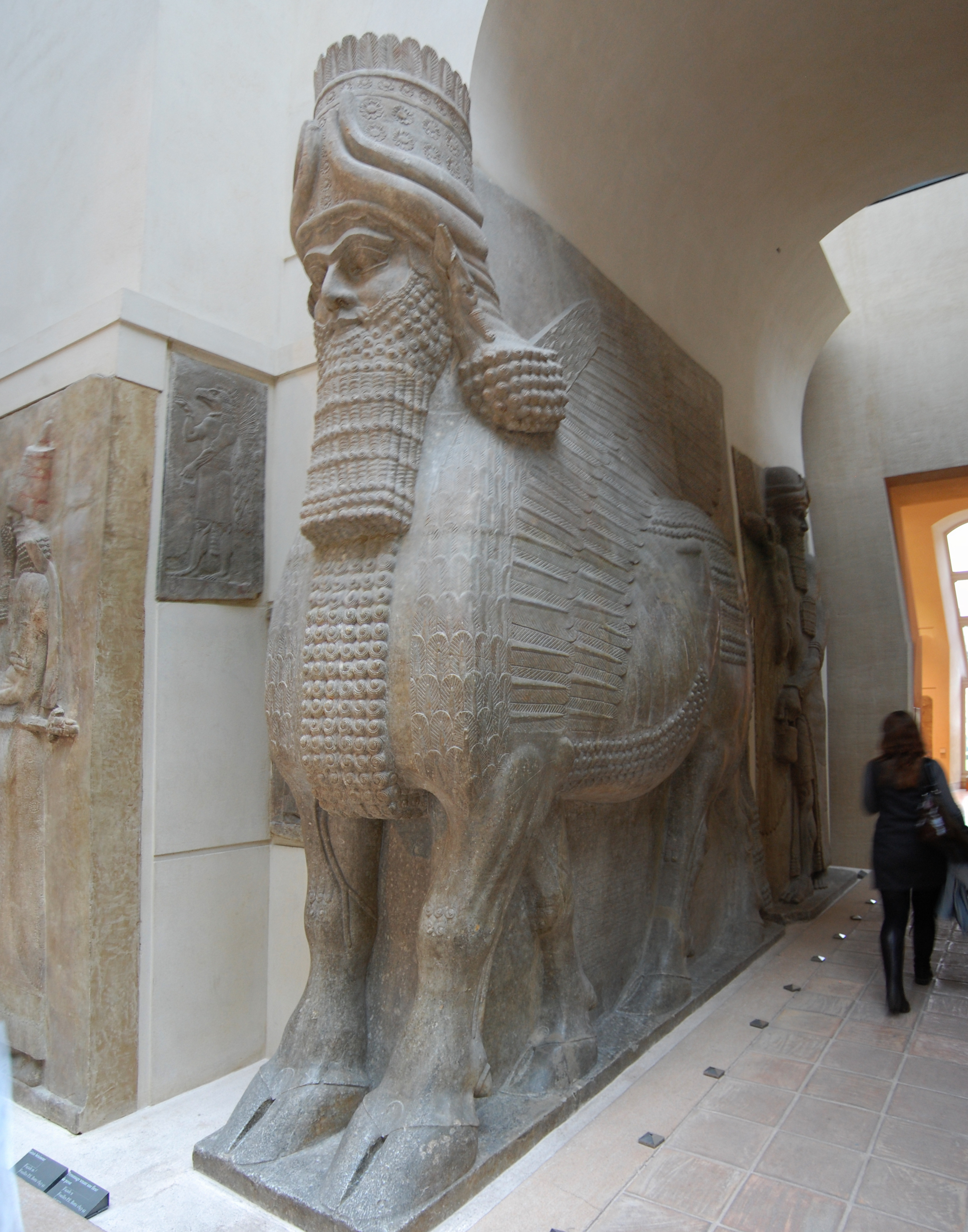 the winged human headed bull Winged human-headed bulls, the powerful guardians of ancient assyrian gateways, serving such a purpose for the royal plalace of nimrud (near mosul in modern iraq) and set in a sympathetic reconstruction at the british museum.