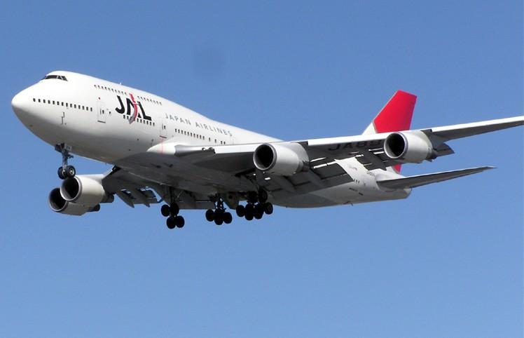 A Boeing 747-400 aircraft in mid-air, with blue sky in the background
