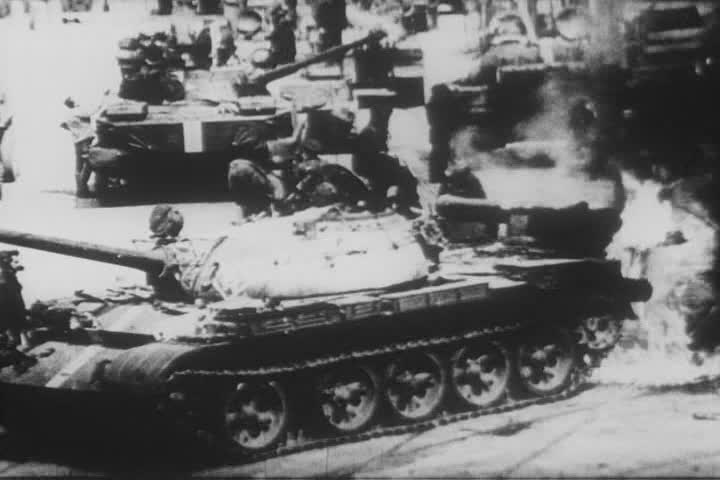 A Soviet T-55 tank catches fire while battling Czech protesters during the 1968 invasion of Czechoslovakia.