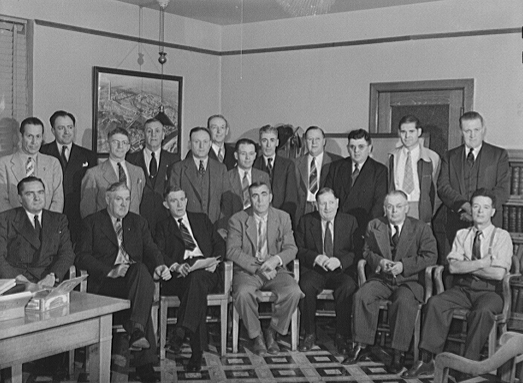 The victory labor-management production committee of the Butte mines, September 1942. In the back row from left to right are: J.A. Livingston, Anacoda Copper Mining Company; E.I. Renouard, assistant general superintendent, ACM; H.J. Rahilly, assistant general superintendent, ACM; Charles Black, Butte miners' union; John Downs, boiler makers' union; W.J. McMahon, commissioner of labor of ACM; John F. Bird, electricians' union; J.P. Ryan, foreman of ACM; Ira Steck, superintendent, electrical department of ACM; James Cusick, machinists' union; John J. Mickelson, Butte miners' union; Eugene Hogan, superintendent ACM. In the front row reading from left to right are: S.S. McGlone, general superintendent, ACM; Bert Riley, Butte miners' union; Dennis McCarthy, Butte miners' union; A.C. Bigley, ACM; Carl Stenberg, painters' union; John Eathorne, foreman of ACM; John Gaffney, carpenters' union.