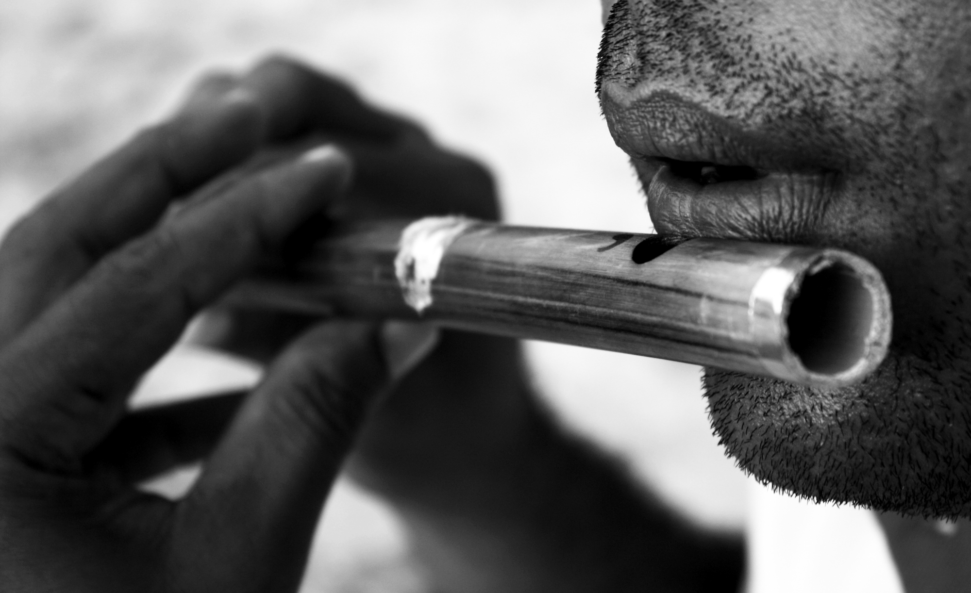 close up of man's mouth and hands while playing the flute