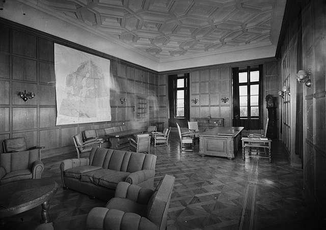 Una imagen en blanco y negro de una habitación grande, con dos grandes ventanas en la pared del fondo, con dos paredes más viniendo lejos de esta pared en ángulo recto.  Hay una serie de grandes sofás espaciadas alrededor de la habitación, así como sillas individuales, y un gran escritorio rodeado de sillas.  En las paredes que no tienen ventanas, uno tiene un gran mapa del norte de Europa, mientras que la otra pared tiene una gran puerta que conduce fuera de la habitación.