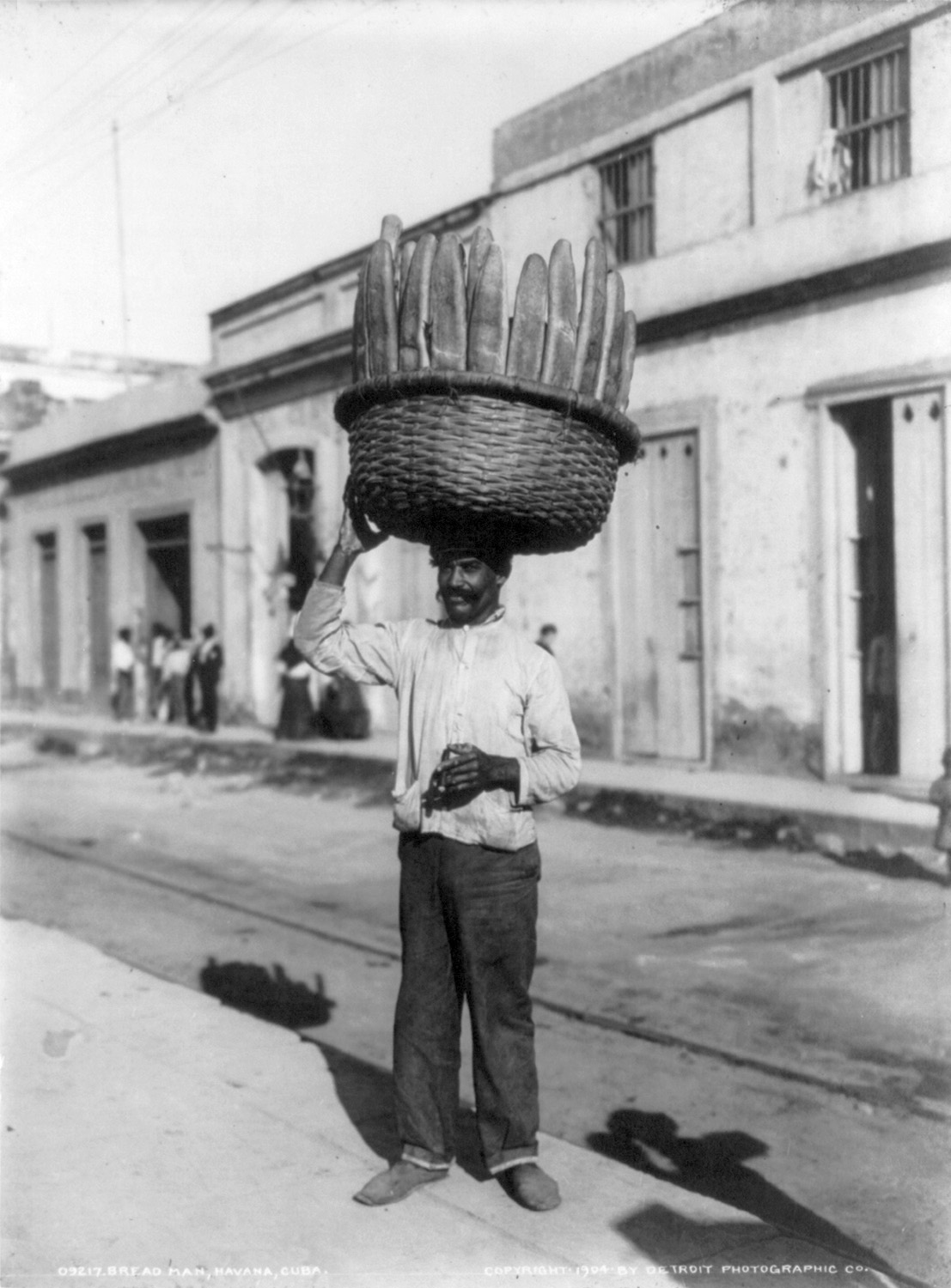 Man carrying a basket of bread on his head, Ha...