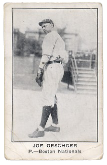 A man wearing a white old-style baseball uniform and dark baseball cap
