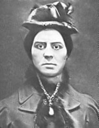 Head-and-shoulders view of a heavy-faced woman with dark hair, wearing a bonnet and a fur-lined coat, with a prominent necklace in front
