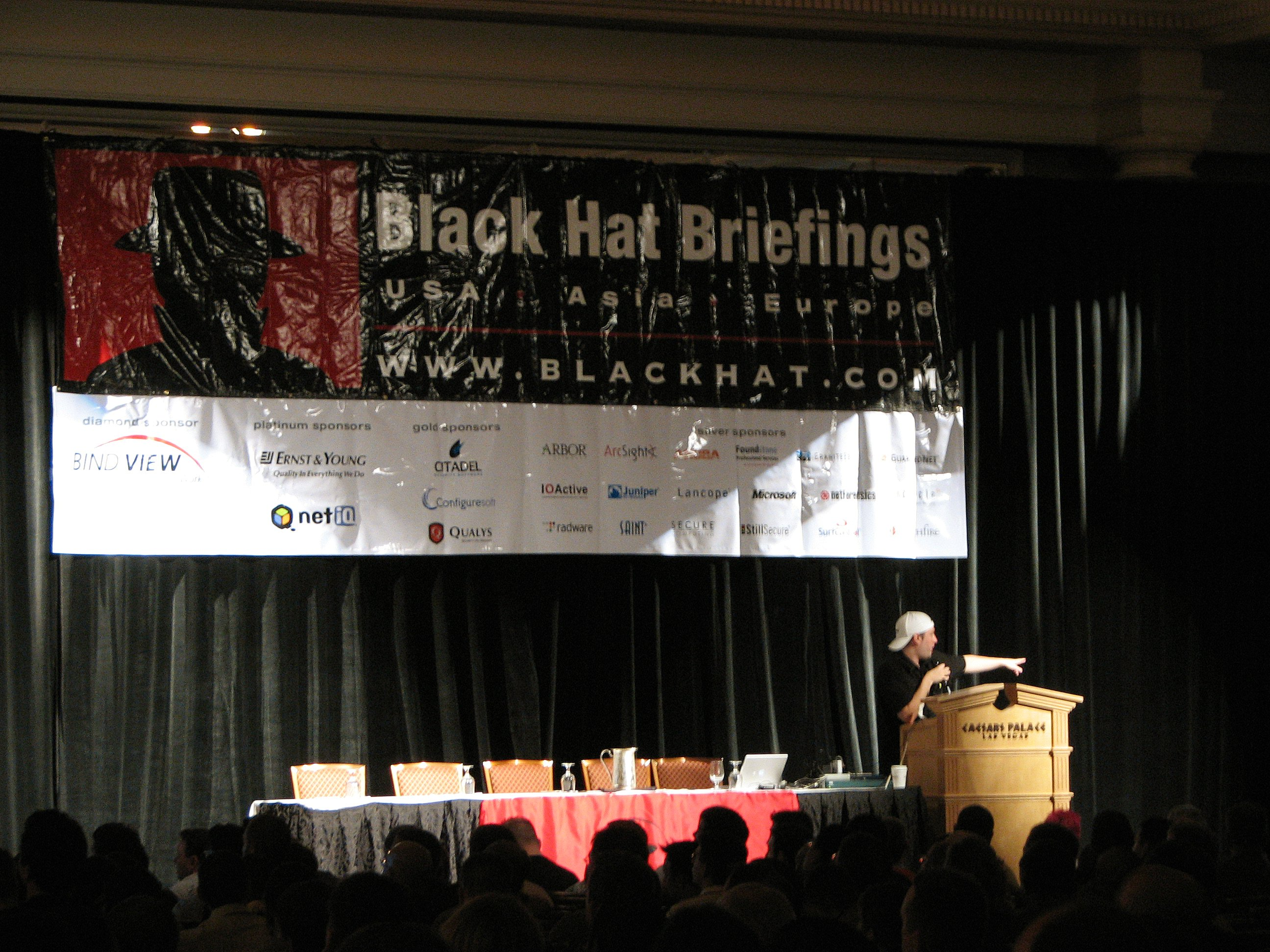 Man in white hat is standing at a podium and speaking to audience with a large banner in the background