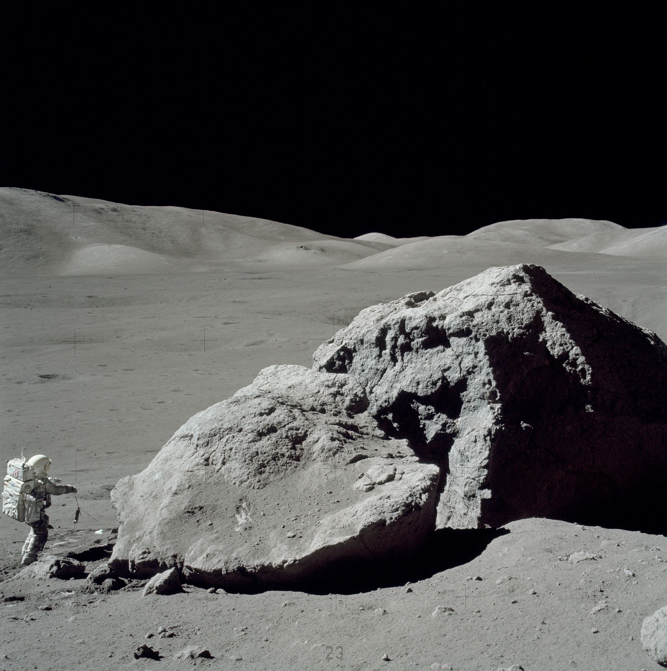 An Apollo 17 crewmember stands next to a boulder on the Moon