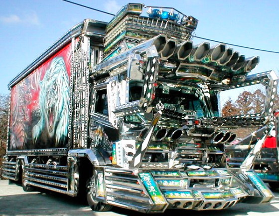 A chrome Dekotora with a red trailer. There is a tiger on this trailer.
