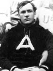 Black and white portrait of a man in a shirt with a letter A on it.