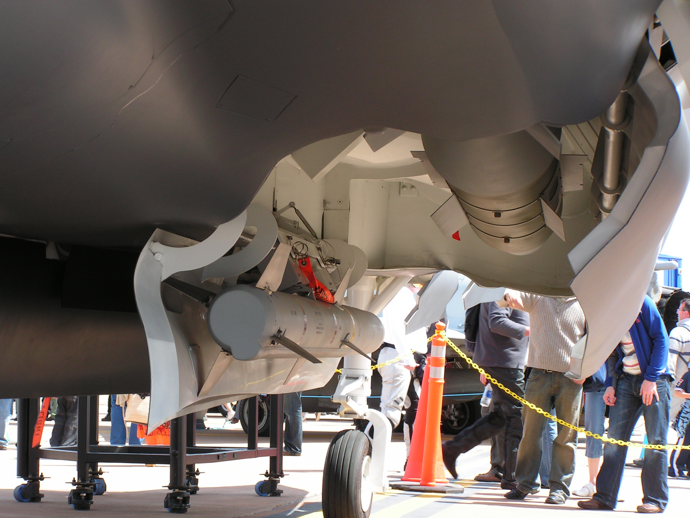 Close-up view of open aircraft weapons bay. The aircraft mock-up itself is on display, watched on by onlookers.