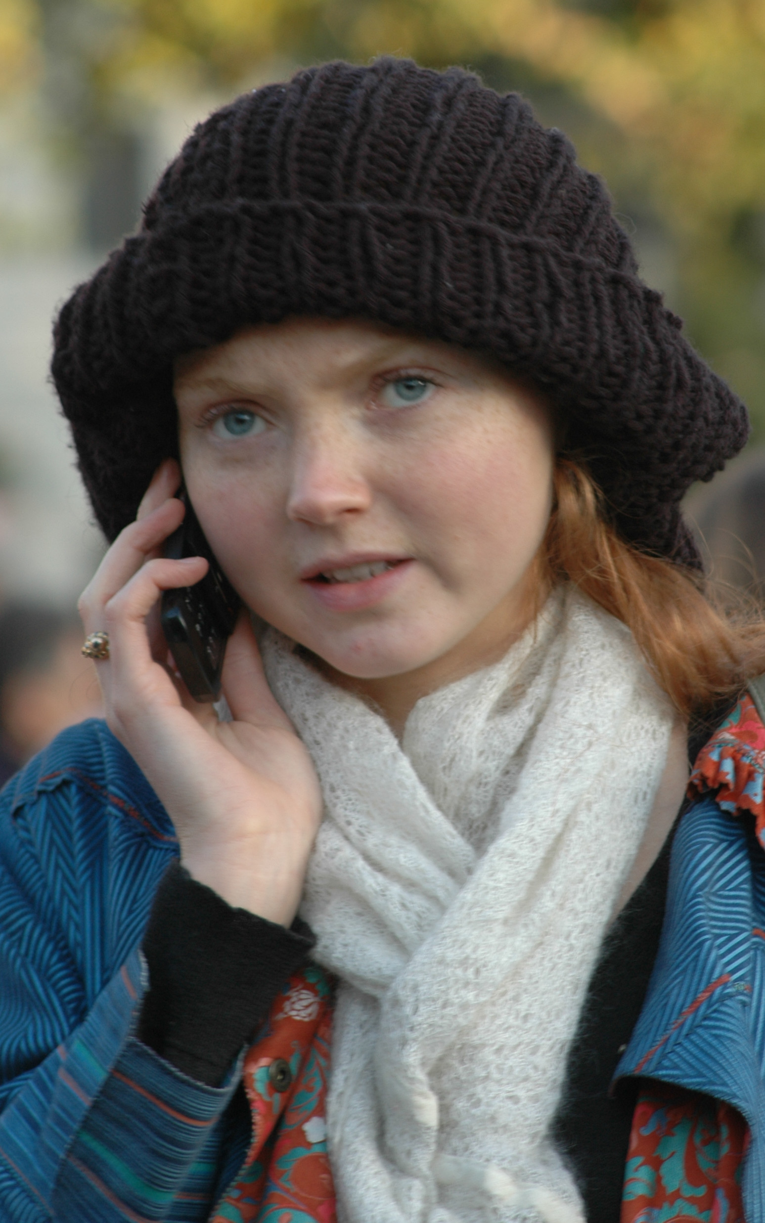 the head and shoulders of Cole outside on a mobile phone wearing a black beret, blue coat and white scarf