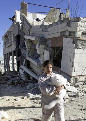 Palestinian girl in front of a demolished home in Balata refugee camp, 2002 Sumayya and her cat in front of her demolished home 2002, 2nd Intifada.jpg