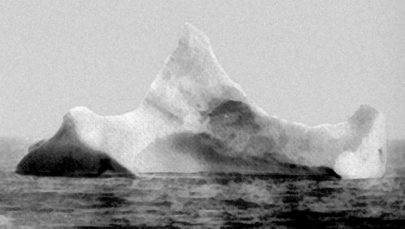 "Black and white photograph of a large iceberg with three ""peaks""."
