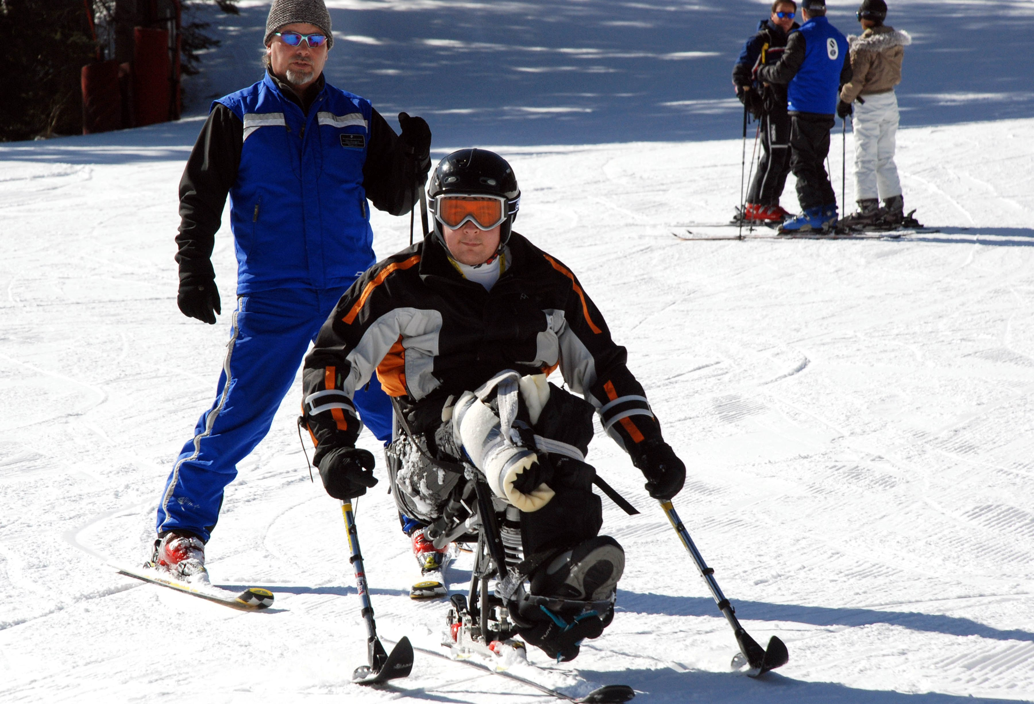 A person without the use of his legs learning to ski on a sit-ski, using two outriggers.