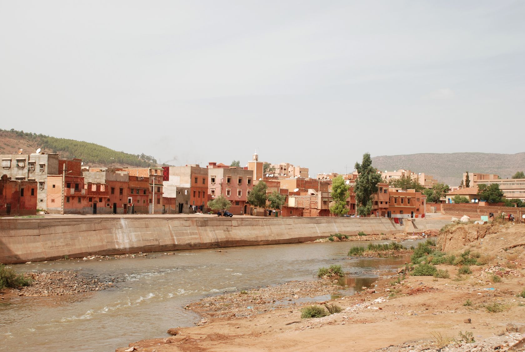 A river runs across the image from left to right with a town in the background, behind a concrete flood defence. The foreground shows a stony, sparsely vegetated river bank.