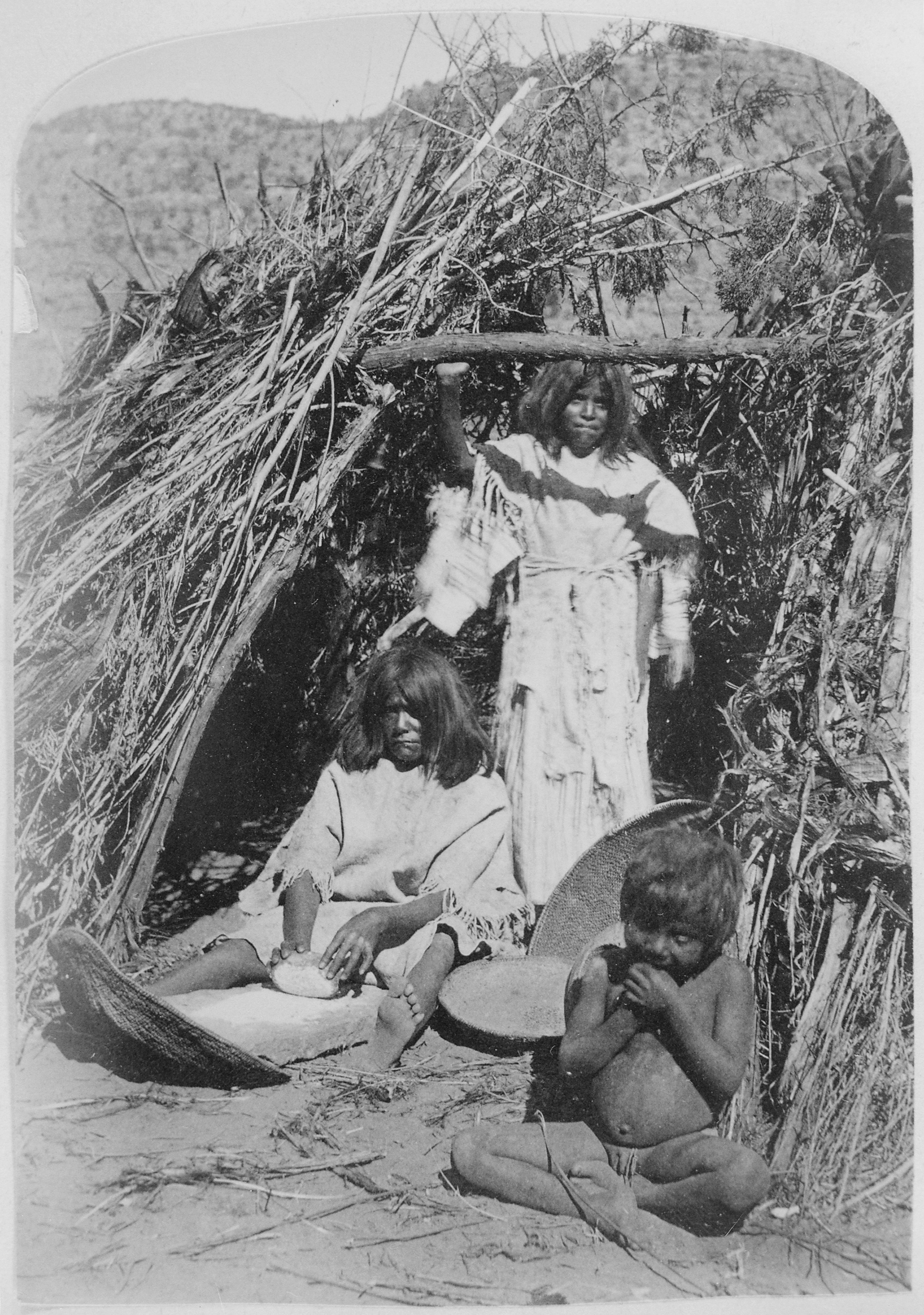 File Paiute Woman Grinding Seeds In Doorway Of Thatched
