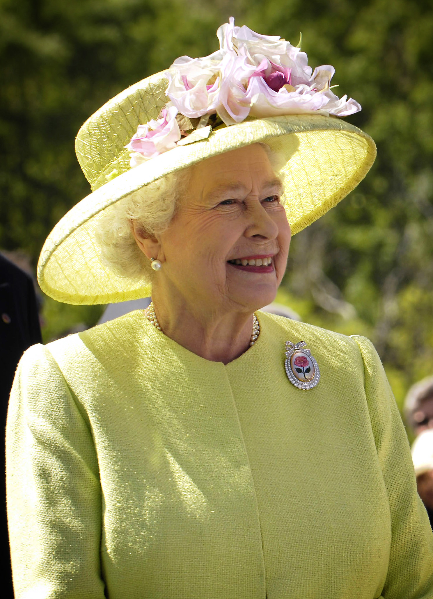 Photo of Queen Elizabeth II in a yellow suit with a lovely hat with flowers surrounding it.