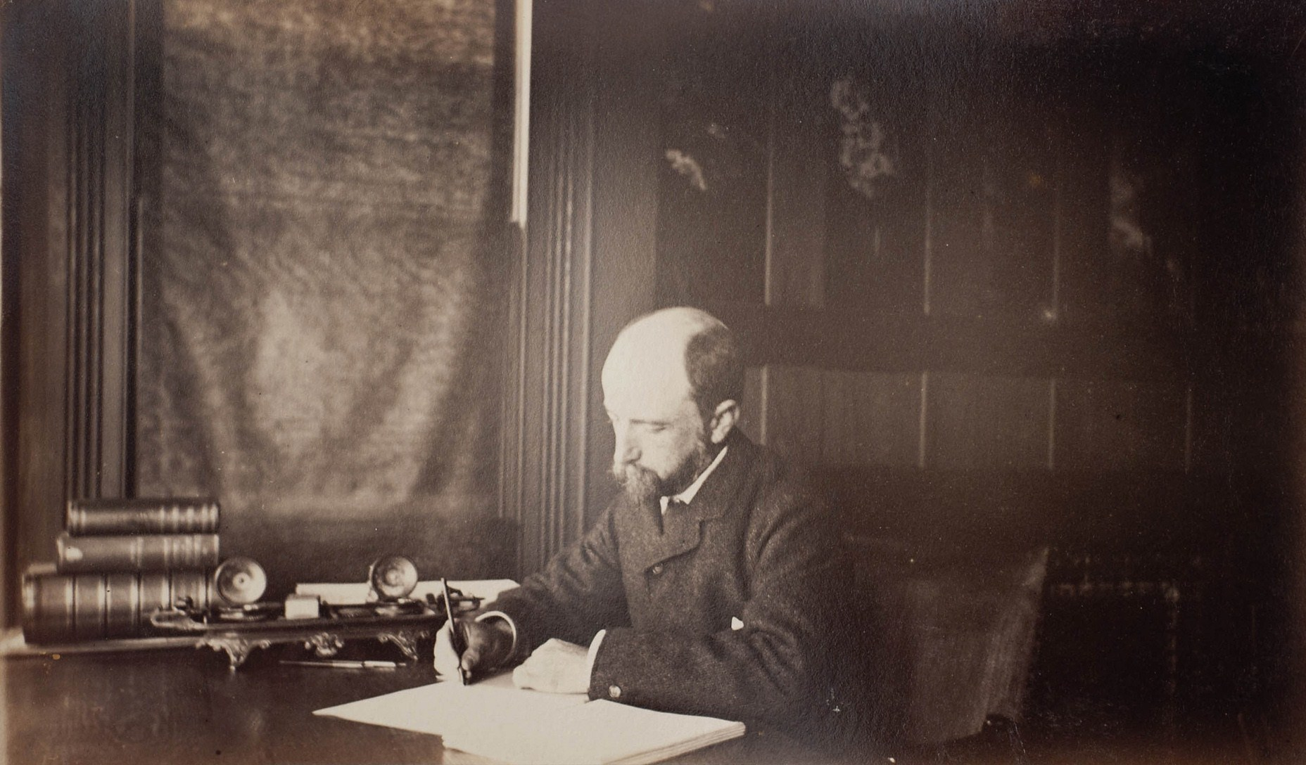 Henry Adams seated at desk in dark coat, writing, photograph by Marian Hooper Adams, 1883.jpg