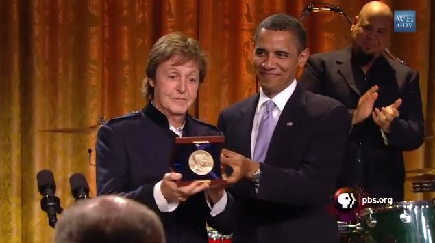 Mcartney being handed an award from President Obama, both men are wearing dark suits, an orange curtain can be seen behind them, as well as drummer Abe Laboriel Jr., who is clapping