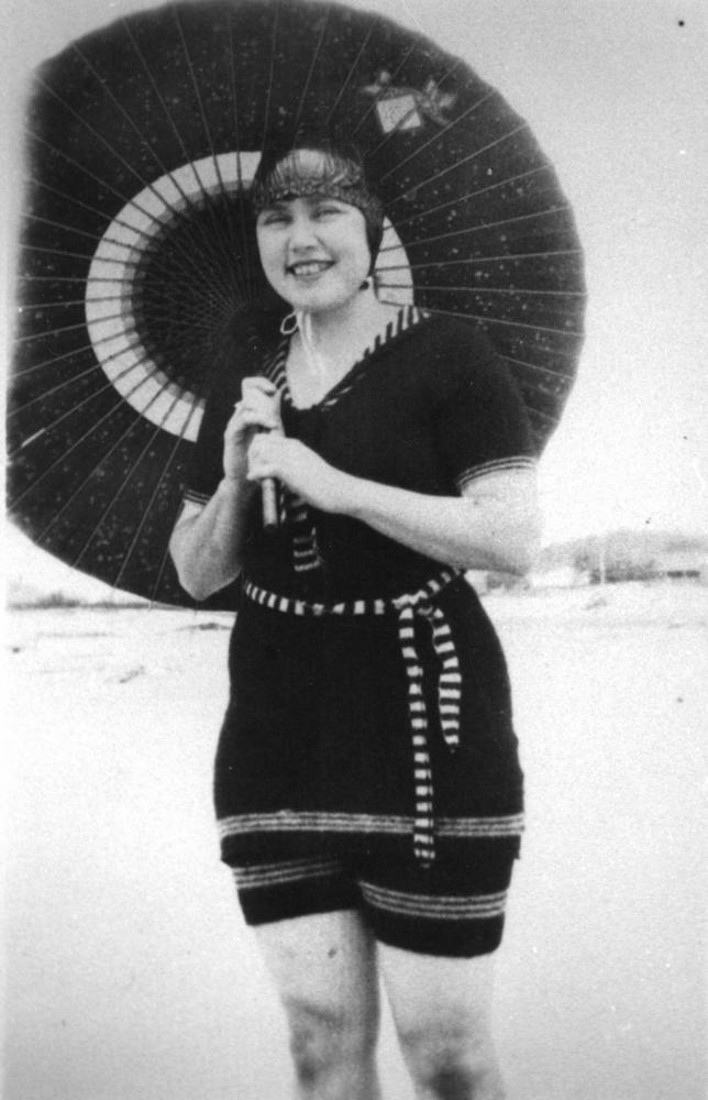 Young lady posing with a parasol on a beach, ca. 1925 image via Wikimedia Commons