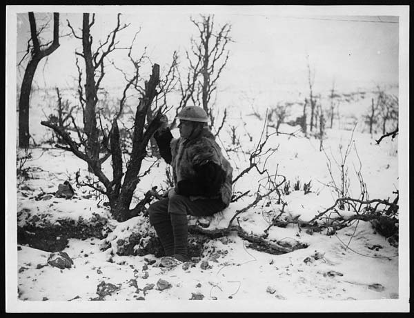 British soldier wrapped up against the cold, Western Front, during World War I. The British soldier in this photograph is sitting in the snow in a wood. He does not have his rifle or other equipment and it appears to be a posed shot to show how he is dressed. Over his uniform jacket, he is wearing an animal-skin waiscoat with the hair side out. This may be one of the goatskin jackets issued in 1915. These gave a bit of additional warmth but quickly got wet through and became very smelly.The uniform at the beginning of the war was not suitable for the varied weather conditions of such a long, static conflict. After the failure of the normal greatcoats and the goatskin jackets, sleeveless leather waistcoats with a warm cloth lining were issued in 1916. These proved more suitable and remained in use. Many men also added extra non-uniform jumpers, scarves and gloves. [Original reads: 'A well clad British soldier.'] http://digital.nls.uk/74549266