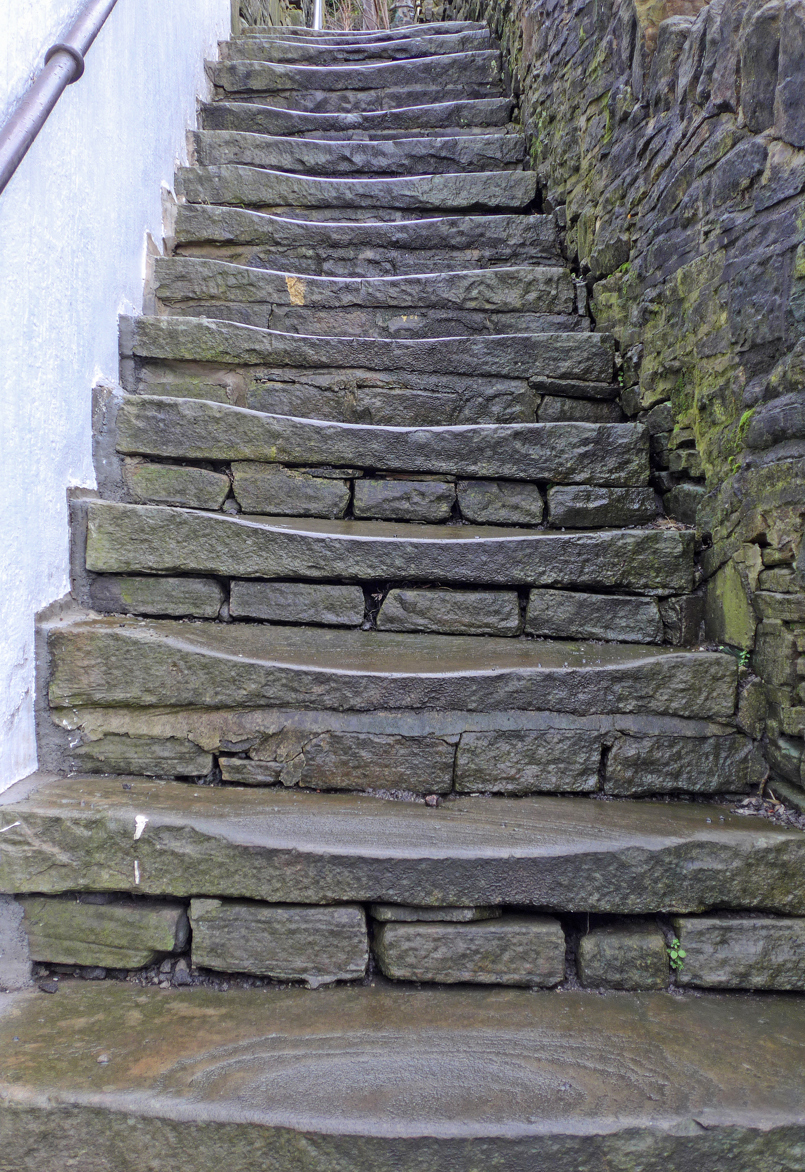 Stone steps worn away in the center under years of footsteps