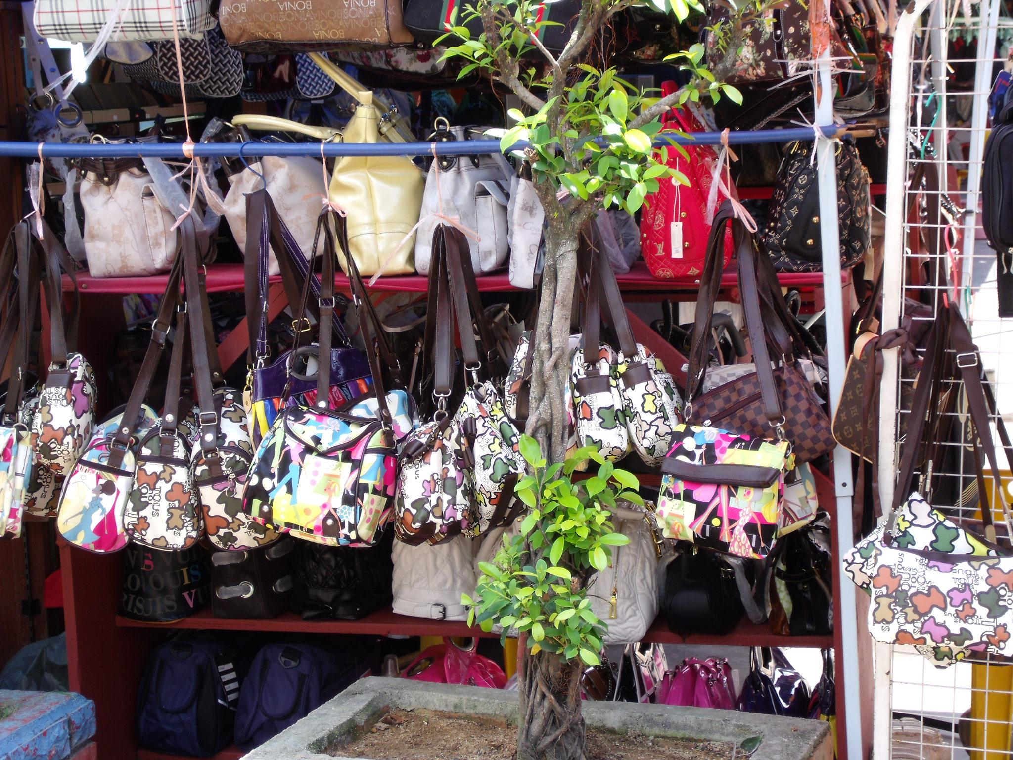 Counterfeit LV bags at a roadside shop in India. Photo credit: User: (WT-shared) Traveller at wts wikivoyage/via Wikimedia Commons [Public Domain].