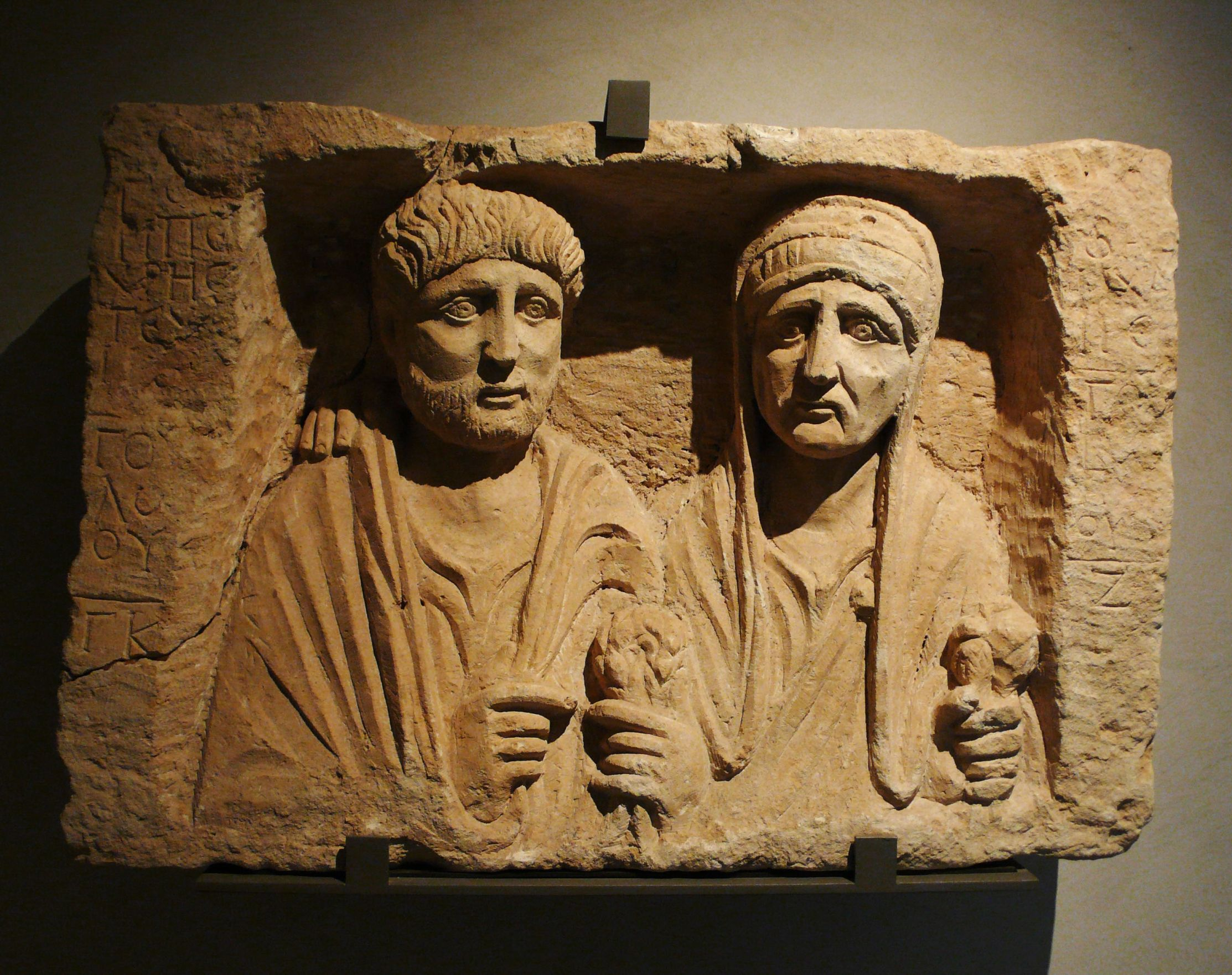 Ancient Roman limestone funerary stele depicting a man and