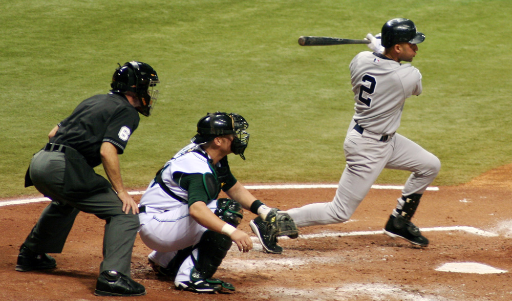 A baseball player in a grey uniform follows through with his swing, while a catcher on the opposing team in a white uniform squats behind him and an umpire in a black uniform stands behind the catcher.