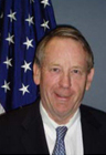 Smiling man with thinning hair wearing a suit and a blue tie with the US flag behind him