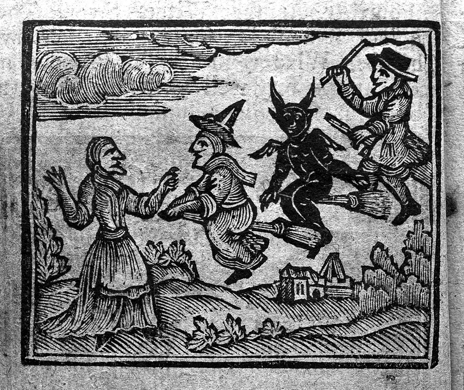 Woman greeting beings arriving on broomsticks