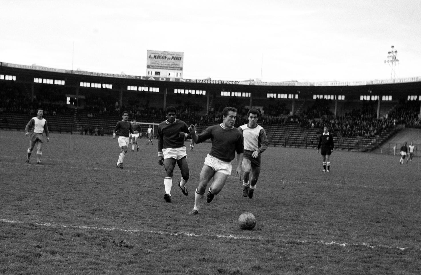 Toulouse Football Club rencontre l'équipe de Nîmes. Cliché pris durant le match. Au 1er plan action de jeu ; en arrière-plan gradins avec spectateurs