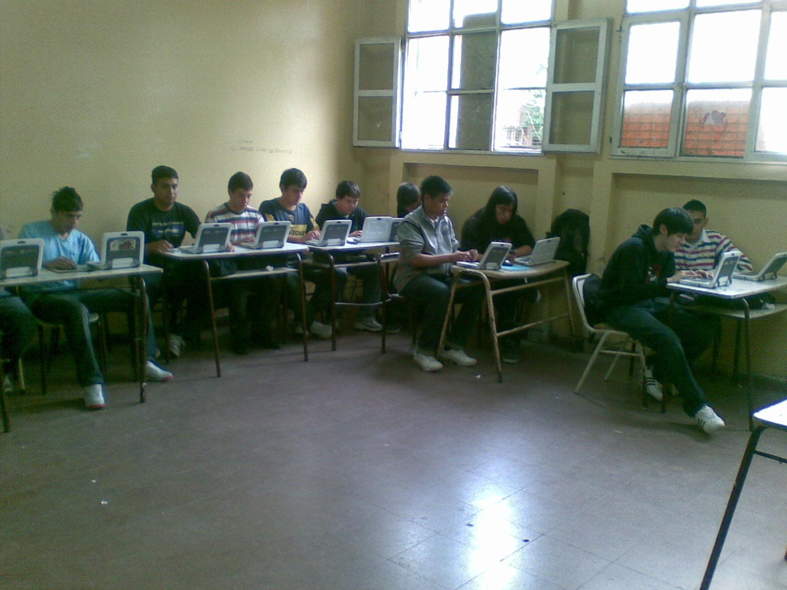 Alumnos de una escuela tecnica trabajando con computadoras. Se observa una disposición tradicional del espacio aulico.
