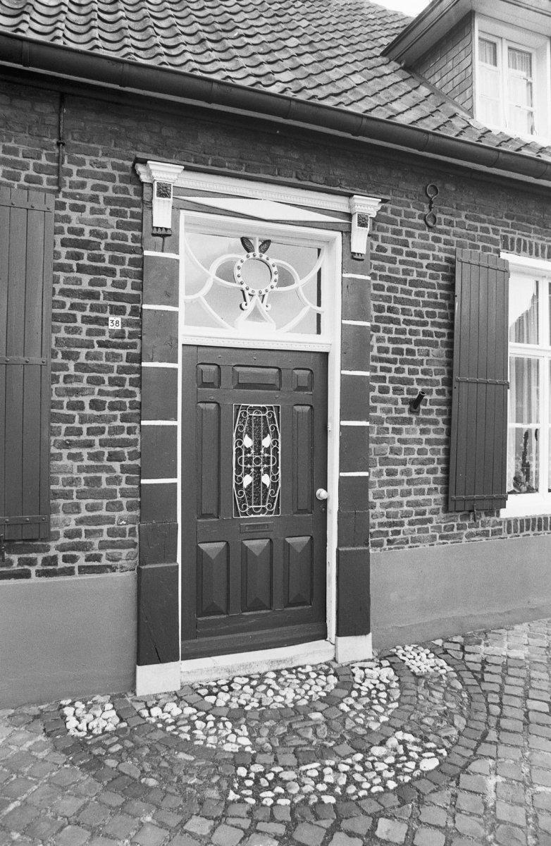 Huis bestaande uit twee vleugels naast elkaar onder zadeldaken tussen topgevels met vlechtingen - Een gang ingang ...