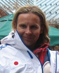 A smiling man with long dark blond hair and a piercing in his left eyebrow is wearing a white winter sports coat over a red jacket; the white coat has a white badge with a red circle in the center.