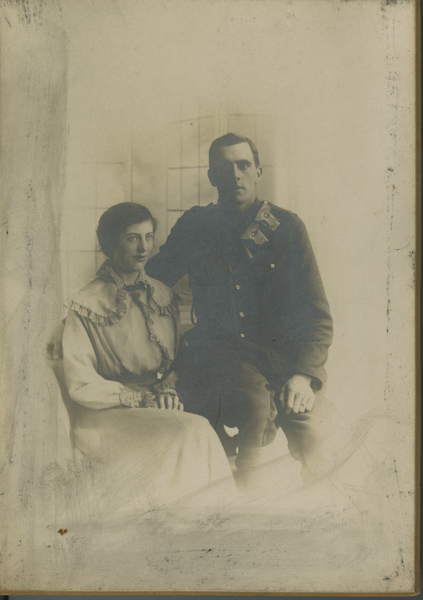 File:Photograph, sepia, mounted studio photograph showing a young woman and a soldier (in uniform with bandolier). Both are seated. Woman has a dress with small shoulder cape with frills down front and on (16025936632).jpg