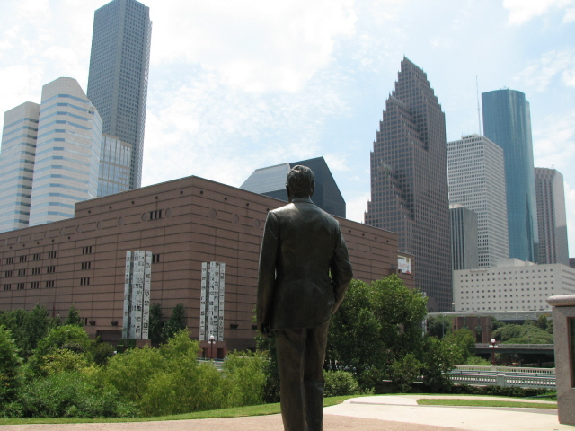 George H.W. Bush statue in Sesquicentennial Park looking towards the Downtown Houston skyline