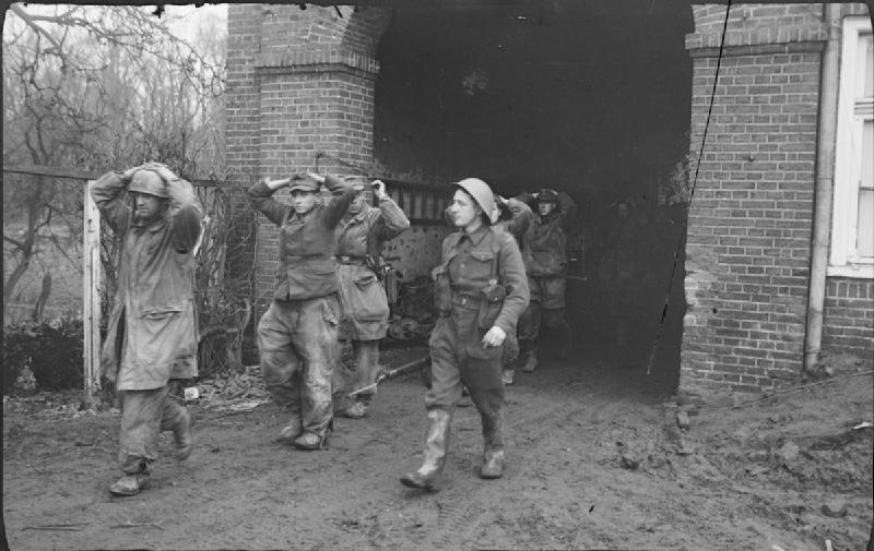A Canadian soldier escorts captured German parachute troops