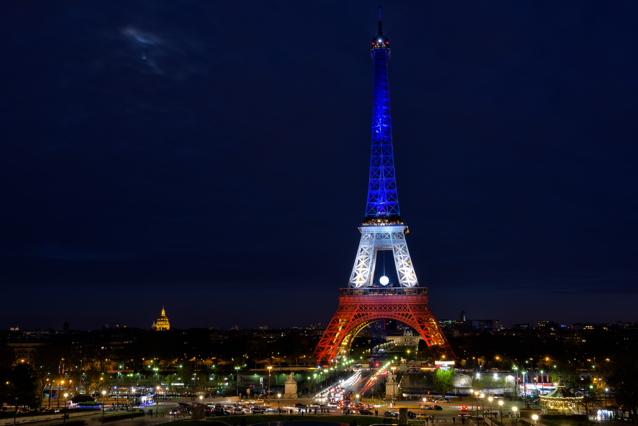 The eiffel tower illuminated in the colors of the french flag