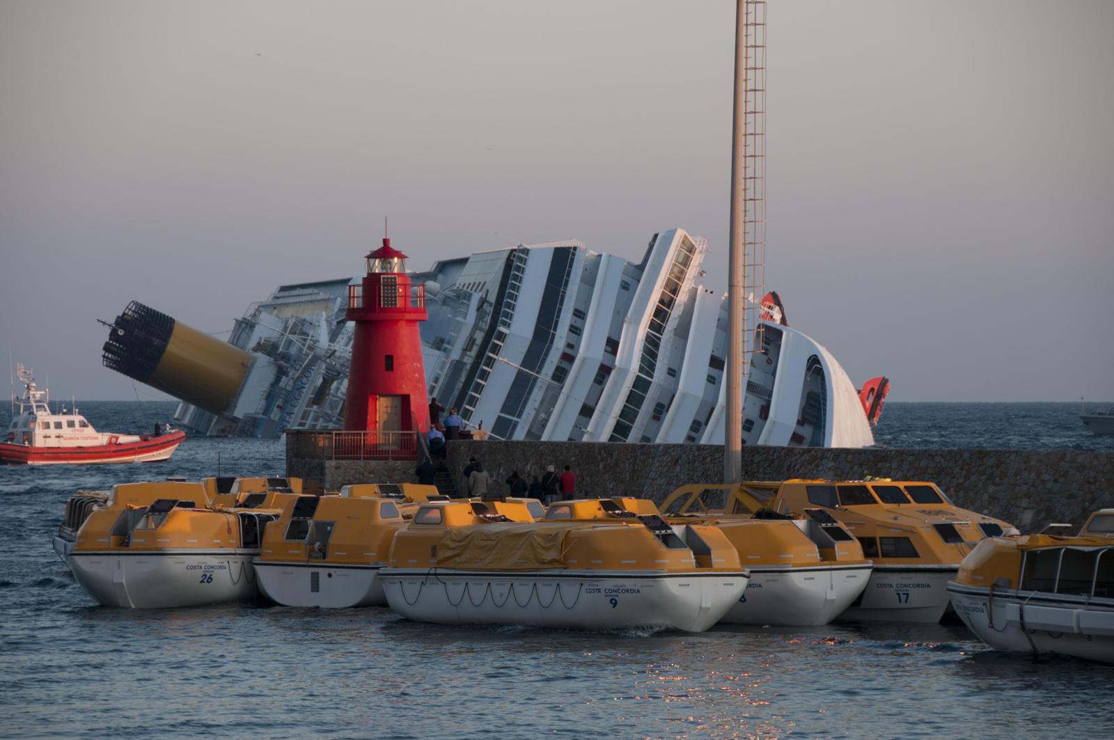 La Costa Concordia semisommersa di fronte all'Isola del Giglio. In primo piano le lance usate per l'abbandono della nave, ormeggiate nel porto.