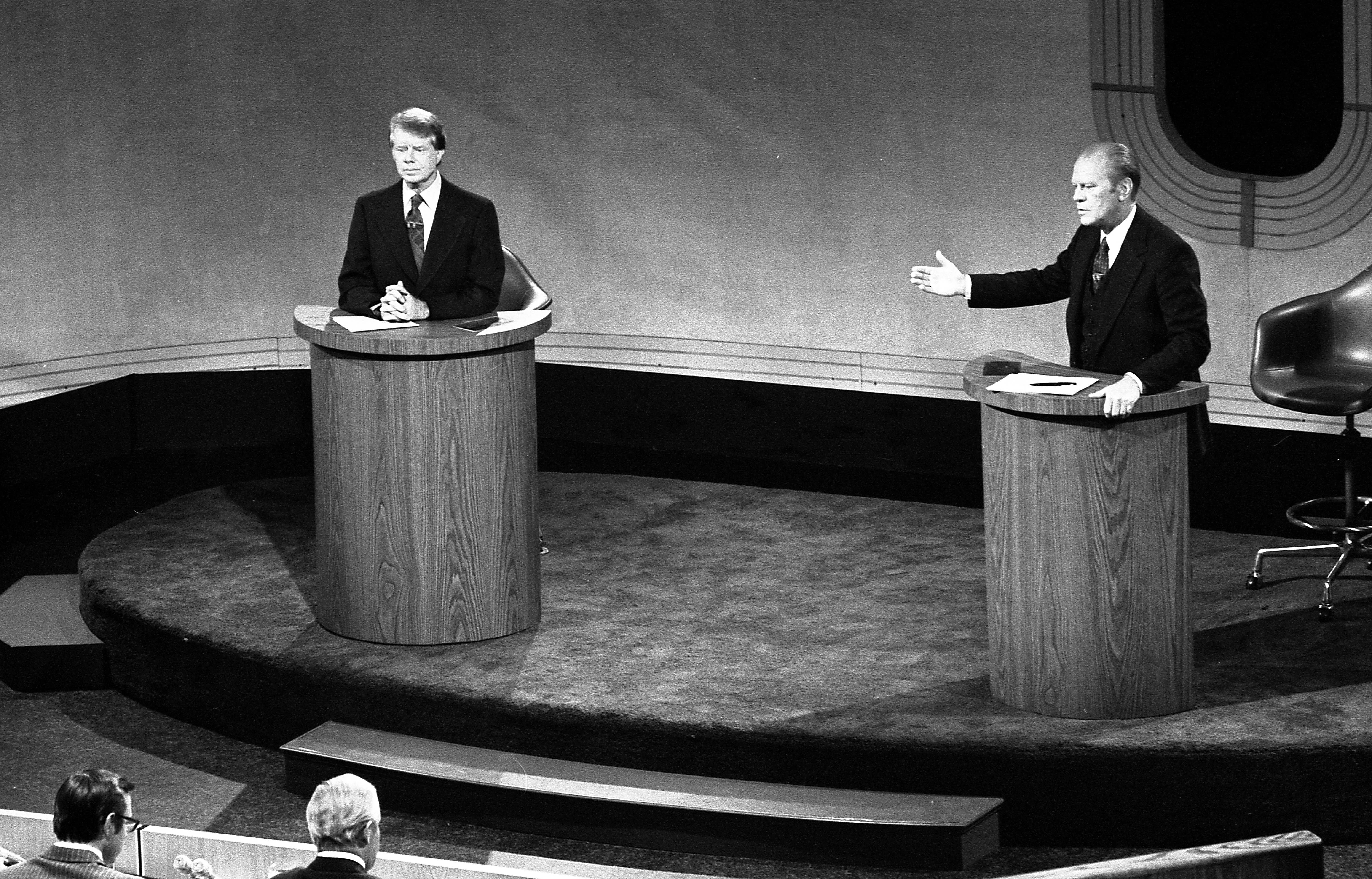 Two men stand at podiums on a stage. The man on the right is speaking while gesturing to the man on the left. Two other men are seated, facing the podiums.