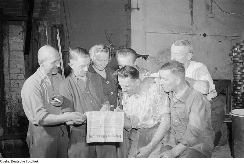 Arbeiter beim Lesen einer Zeitung. 1952. Urheber: Roger Rössing. Deutsche Fotothek. Lizenz: CC-BY-SA-3.0-DE.
