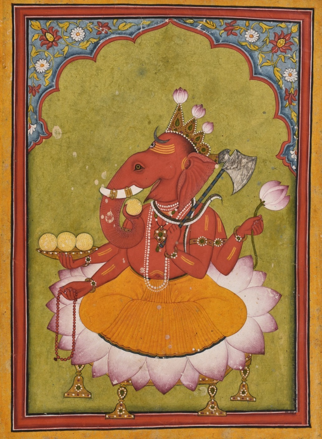 Attired in a an orange dhoti, an elephant-headed man sits on a large lotus. His body is red in colour and he wears various golden necklaces and bracelets and a snake around his neck. On the three points of his crown, budding lotuses have been fixed. He holds in his two right hands the rosary (lower hand) and a cup filled with three modakas (round yellow sweets), a fourth modaka held by the curving trunk is just about to be tasted. In his two left hands, he holds a lotus above and an axe below, with its handle leaning against his shoulder.