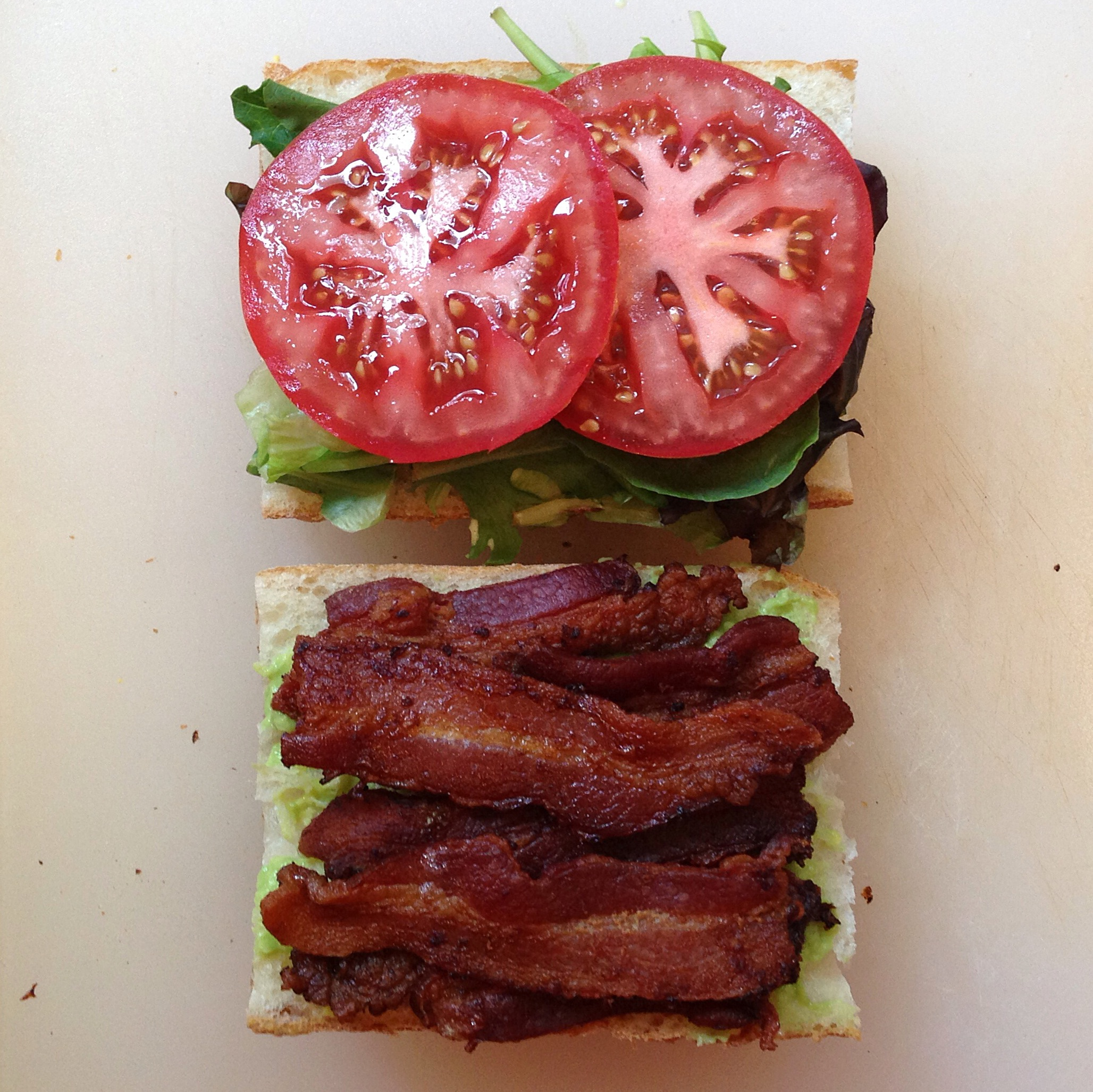 A BLT sandwich laid out on two slices of bread before being put together