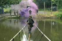 Cadets cross a rope bridge during summer training