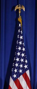 A U.S. flag with gold fringe and a gold eagle on top of the flag pole