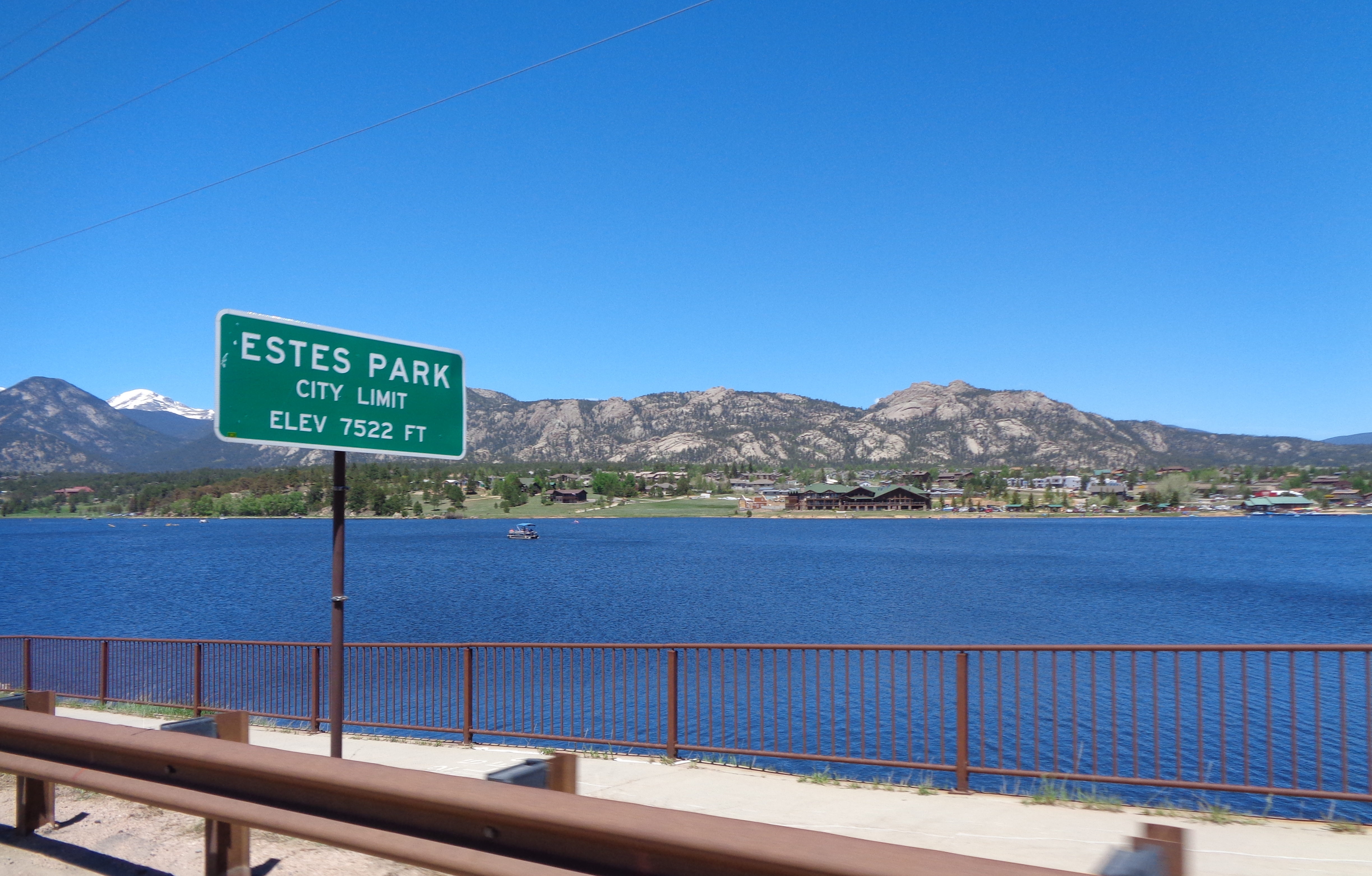 An Estes Park City Limit sign welcomes passersby on a bridge into town
