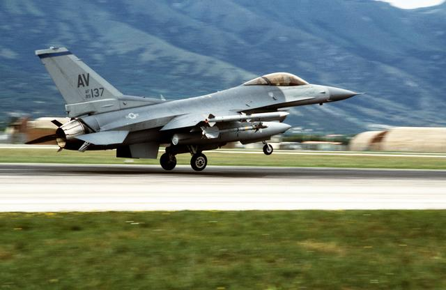 A fighter jet with AV marked on its tail takes off from a mountain runway.