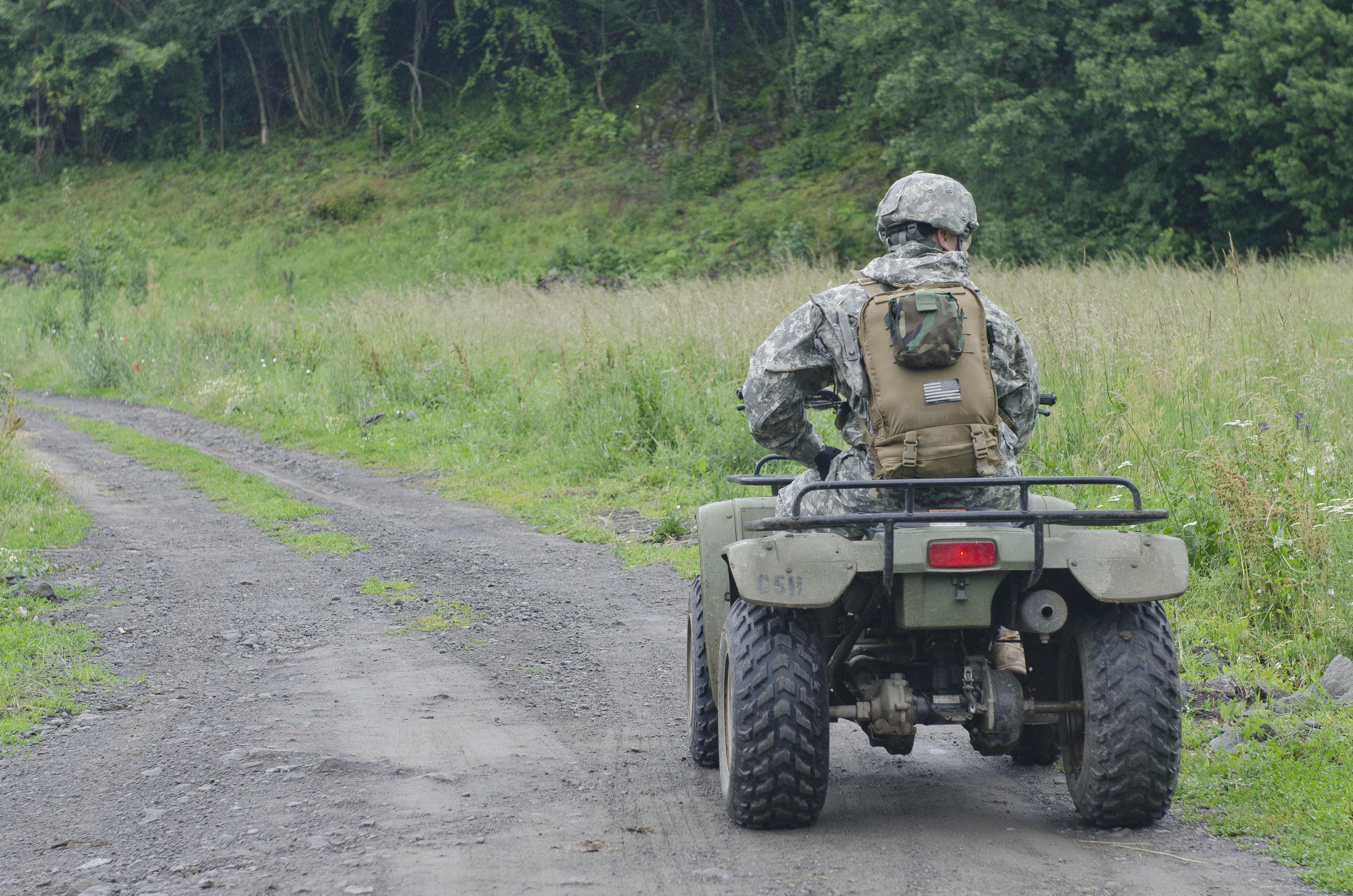 Soldier riding an ATC down a dirt road.